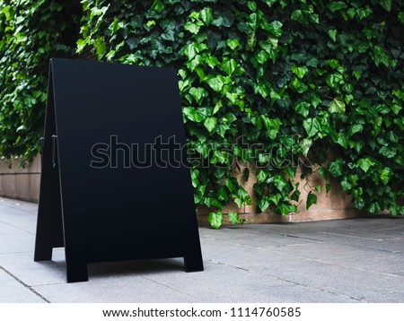 Blank Board stand mock up Black metal Signage Outdoor green garden background #1114760585