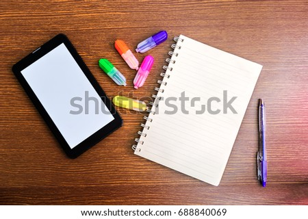 Blank book, colored pen and ipad set on wooden desk. #688840069