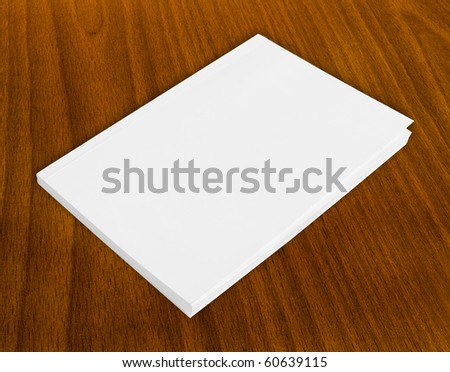 Blank book with white cover on wood background.