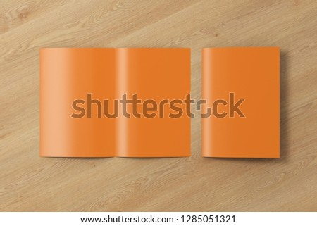 Blank brown open and folded half-folded flyer leaflet on wooden background. With clipping path around brochure. 3d illustration