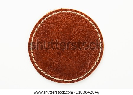 Blank brown round leather label on white background, macro close up