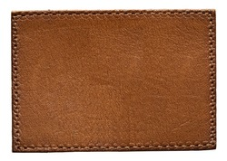 Blank brown round leather label on white background, macro close up. Leather patch with stitching