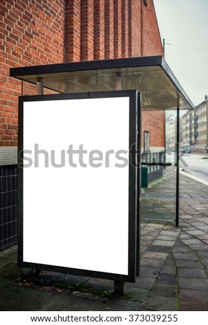 Blank bus stop advertising billboard on empty street as copy space for outdoor poster ad mock up.