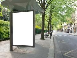 Blank bus stop billboard Mockup in empty street in Paris. Parisian style hoarding advertisement close to a park in beautiful city