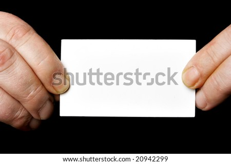 Blank business card in hands over black background