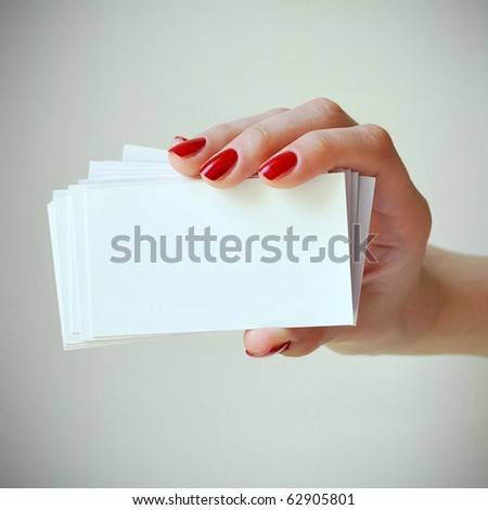 Blank business cards in elegant female hand with red nails