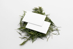 Blank business cards in the pile of green, grass tea on a white background, packaging mockup with empty space to display your branding design.