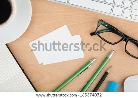 Blank business cards with supplies and coffee cup on wooden office table