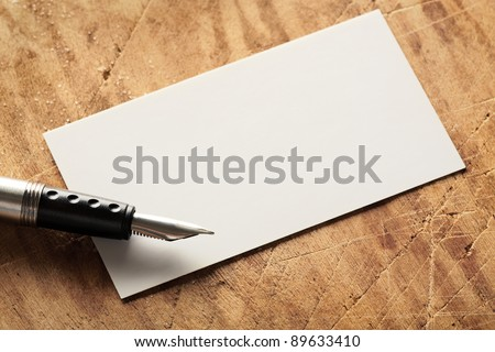 Blank business (visit) card on old wooden table with fountain pen.