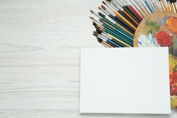 Blank canvas, brushes and palette on white wooden table, flat lay. Space for text