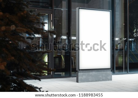 Blank canvas illuminated white outdoor banner stand next to glass facade of modern building at downtown at night time. Empty outdoor billboard next to business or commercial center. 3d rendering.