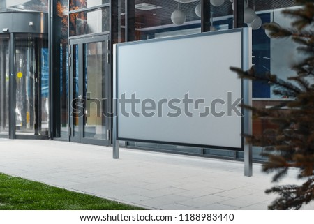 Blank canvas white horizontal outdoor banner stand next to glass facade of modern building at downtown. Empty outdoor billboard next to business or commercial center. 3d rendering.