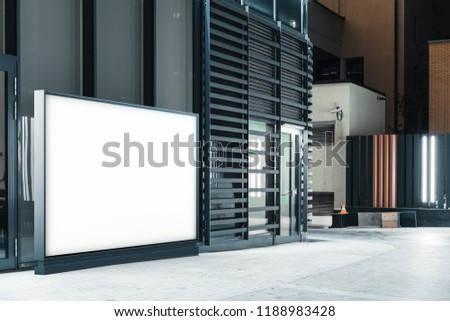 Blank canvas white outdoor banner stand next to glass facade of modern building at downtown. Empty outdoor billboard next to business or commercial center. 3d rendering.