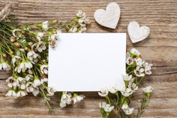 Blank card among chamelaucium flowers (waxflower) on wooden background