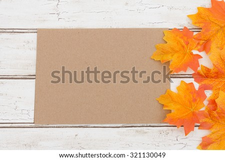 Blank Card for your fall message, A brown card that is blank over a distressed wood background with autumn leaves