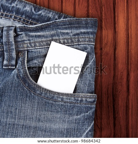 blank card in jean pocket on the wooden background