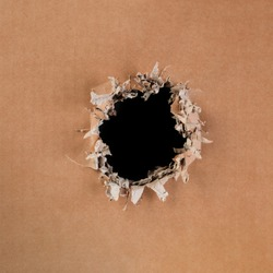 Blank cardboard with rough, ripped and torn hole in the center with blank black space