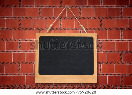 blank chalkboard hanging on brick wall
