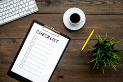 Blank checklist with space for ticks on pad on office desk. Checklist for office worker, manager, businessman, chief on dark wooden background top view