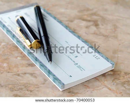 Blank cheque and pen on the table - stock photo
