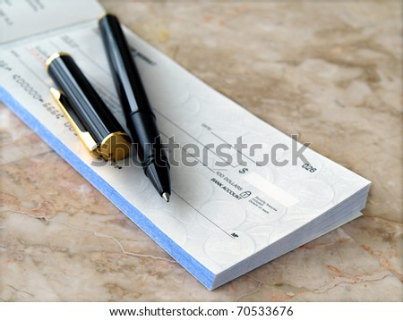 Blank cheque with pen on the table