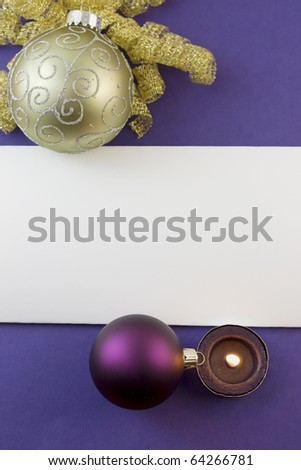 blank Christmas card with gold scroll ornament, purple bauble, tea light candle and copyspace