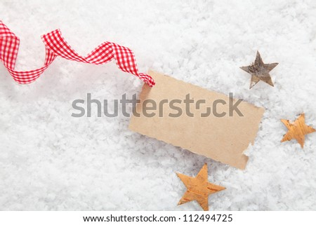 Blank Christmas gift label with a decorative red and white checked rustic ribbon surrounded by stars on fresh winter snow