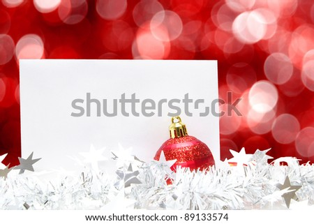 Blank Christmas greeting card with bauble, garland and abstract red light background