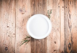 Blank clean white plate on wooden table. Food invitation. Ready to serve and cook fresh meal. Copy empty space. Topview - up high overhead