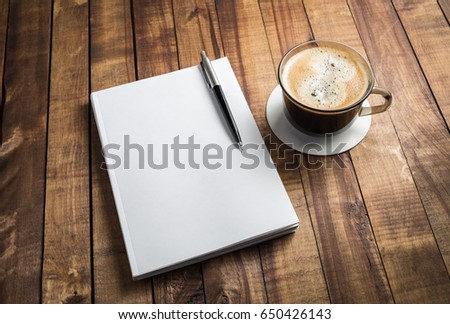Blank closed booklet, pencil and coffee cup on vintage wood background. Responsive design mockup.