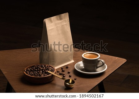 Blank coffee packaging on a wooden table, with pot, coffee seeds bowl, copper spoon, cup with coffee on a wooden background, coffee packaging mockup with empty space to display your branding design.