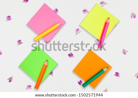 blank colorful sticky notepads with color pencils on a canvas surface covered with tiny flowers. Empty space for text