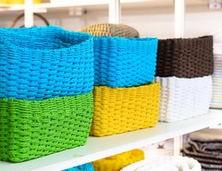 Blank colorful woven baskets. Drawn up in a pile on a shelf.