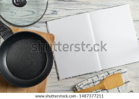 Blank cookbook for your tex, flat lay composition with frying pan on wooden table