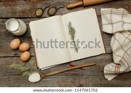 Blank cookbook with some ingredients on the wooden table, top view, rustic style