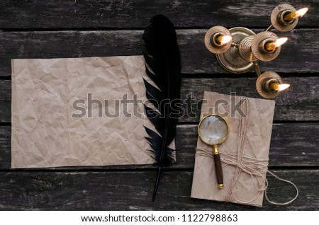 Blank crumpled paper page letter, loupe magnifier, feather ink pen and wrapped in jute rope envelope on old table background. Old message. #1122798863