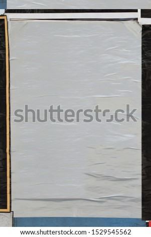 Blank crumpled paper poster plastered on dirty wall. Background design element with copy space to overlay text and photos.