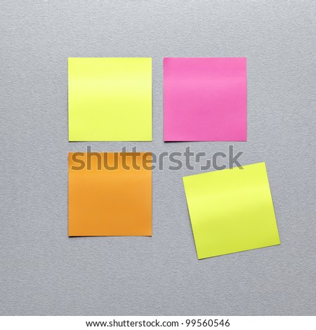 Blank different colors sticky note paper. On gray textured paper background. Closeup.