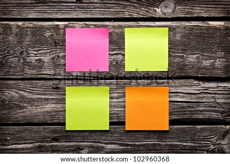Blank different colors sticky note paper sheets. Closeup on old vintage wooden table.