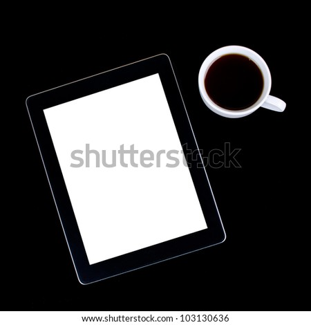 Blank digital black tablet on a desk with empty white screen and cup of coffee