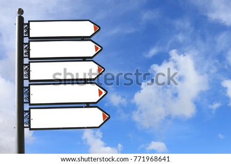 Blank directional road signs against a blue sky. White metal arrows on the signpost #771968641
