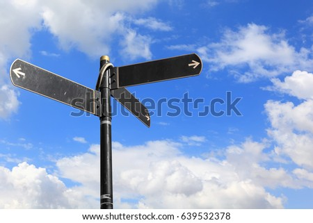 Blank directional road signs against blue sky. Black metal arrows on the signpost #639532378