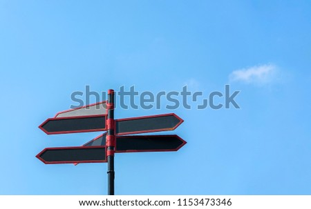 Blank directional road signs against blue sky. Black red arrows on the signpost #1153473346