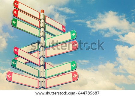 Blank directional road signs against blue sky. White arrows of a various directions on the signpost. Warm toned colors. Old style image   #644785687