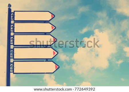 Blank directional road signs against blue sky. White metal arrows on the signpost. Warm toned colors. Old style image  #772649392