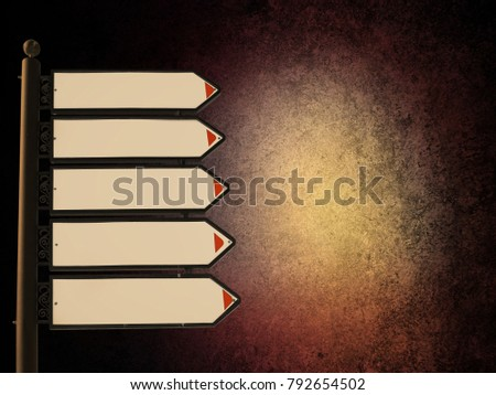 Blank directional road signs against dark grunge background with glowing light spot. White metal arrows on the signpost on rough texture with copy space  #792654502