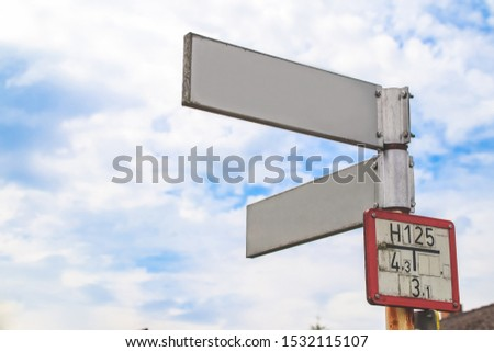 Blank directional road signs White against blue sky.