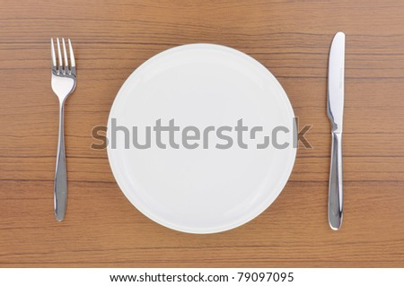 Blank dish, knife and fork on wood table