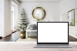 Blank display screen laptop computer on white wood table. Modern cozy comfortable home living room with Christmas decor. Home office desk workspace. Mock up copy space. Winter sales, online shopping