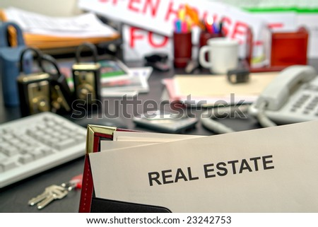 Blank document in an agent presentation binder with real estate title page over successful and busy Realtor desk in realty brokerage sales office with tools of the trade and business supplies